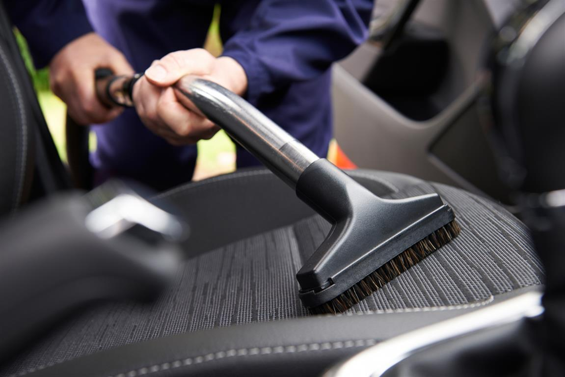 Car interior detailing - Car Interior Detailing Man Vacuuming Seats